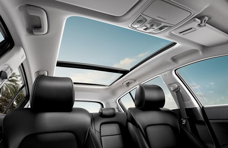 Interior view of the rear seating and panoramic sunroof inside a 2020 Kia Sportage