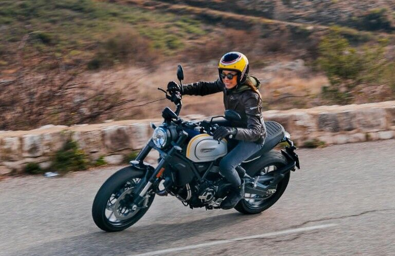 A woman driving a black 2021 Ducati Scrambler.