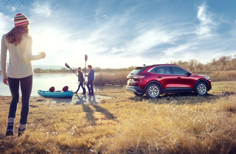 Rear passenger angle of a red 2020 Ford Escape with people getting ready to kayak