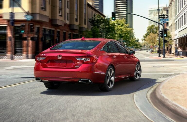 Rear passenger angle of a red 2020 Honda Accord driving on a curving city street