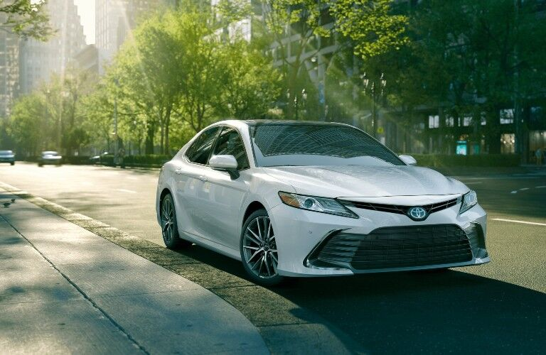 2021 Toyota Camry going down the street with trees on both sides