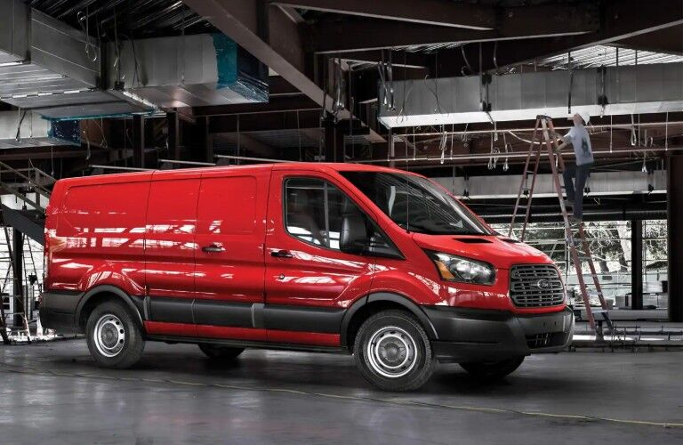 Front passenger angle of a red 2019 Ford Transit parked in a factory