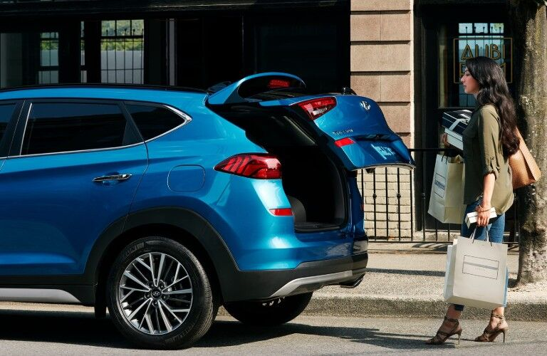 Rear driver angle of a blue 2020 Hyundai Tucson with its liftgate opening and a woman standing behind with bags