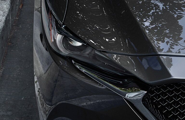 Exterior view of the front headlight on a gray 2020 Mazda CX-5