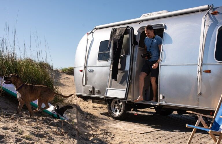 The exterior of a 2020 Airstream Bambi with a man walking outside with his dog.