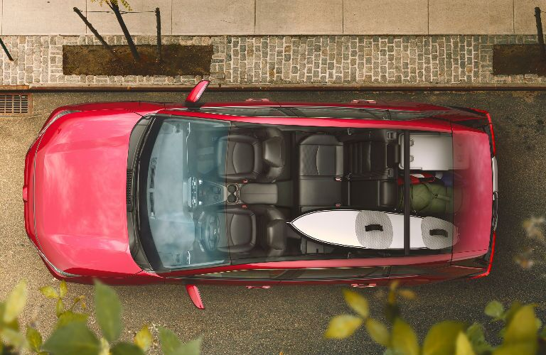 A surfboard in the cargo area of a red 2019 Toyota RAV4