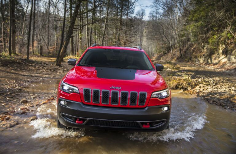 A head-on photo of the 2020 Jeep Cherokee driving through water.