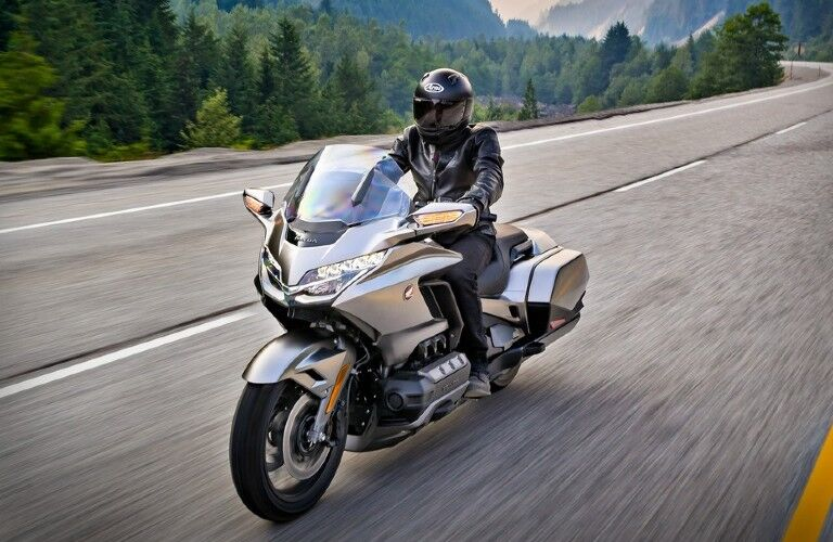 A man riding a silver 2018 Honda Gold Wing down an empty road.