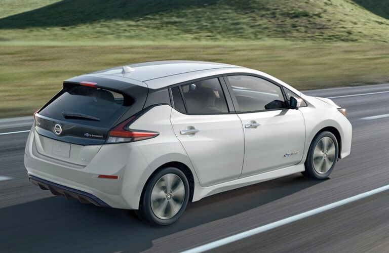 White 2019 Nissan LEAF driving by a grassy field