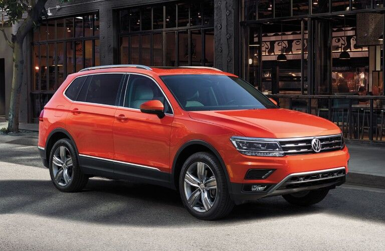 Front passenger angle of an orange 2019 Volkswagen Tiguan parked on the side of a street