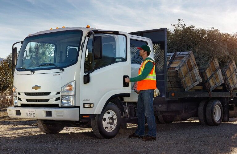 Front driver angle of a white 2019 Chevrolet Low Cab Forward with plants loaded in the back and a worker getting inside