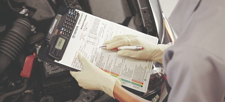 Toyota service technician filling out a service sheet