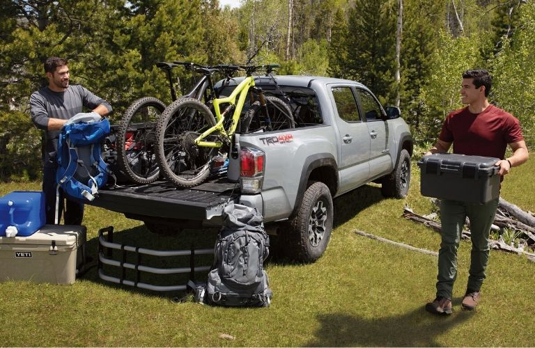2020 Toyota Tacoma with bicycles in the truck bed and two men unloading cargo
