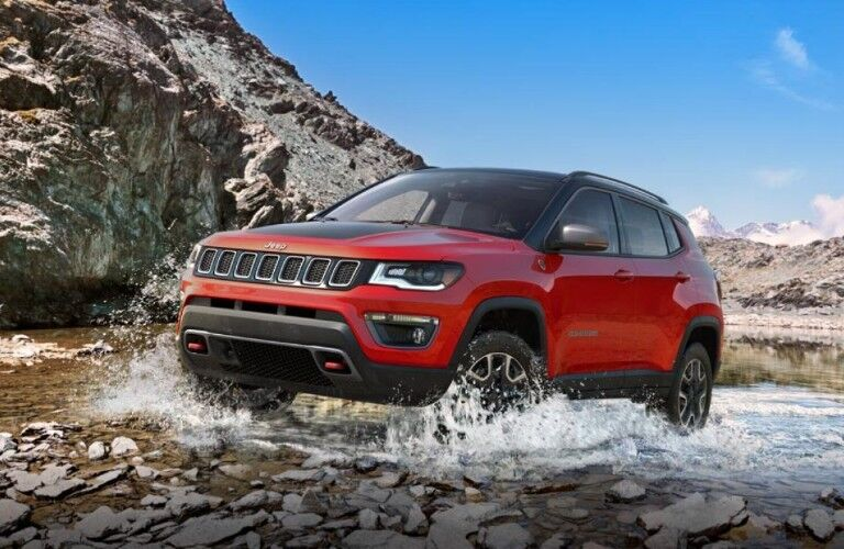 Front driver angle of a red 2019 Jeep Compass driving onto land from a shallow river