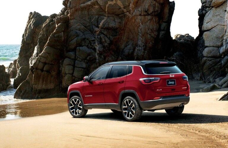 Rear driver angle of a red 2019 Jeep Compass parked on a beach with tall rock formations in the background
