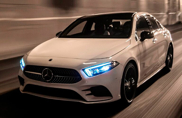 2021 MB A-Class exterior front fascia driver side on blurred highway with headlights on