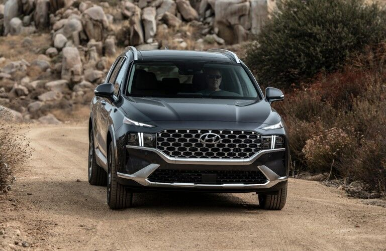 Front exterior view of the 2021 Hyundai Santa Fe while driving on a dirt road