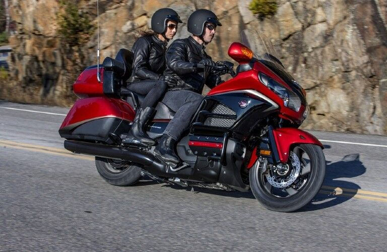 The side view of a couple riding on a red 2015 Honda Goldwing.