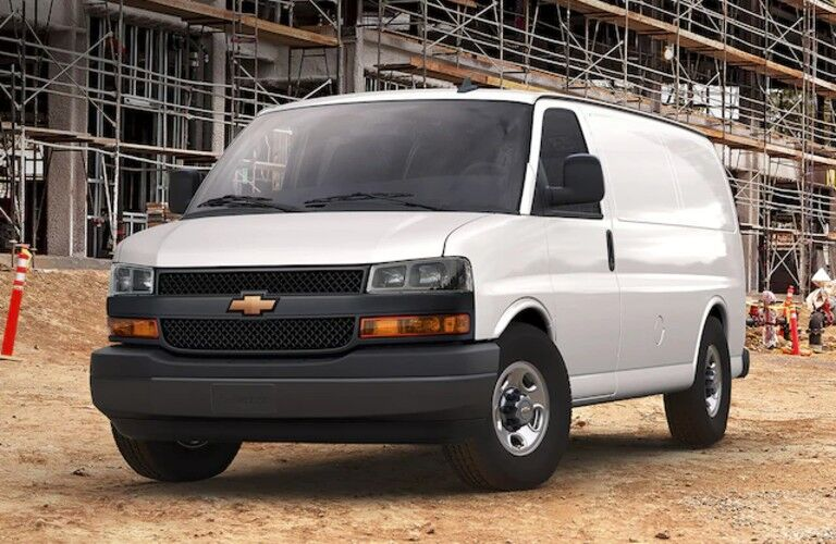Front driver angle of a white 2020 Chevrolet Express parked at a construction site