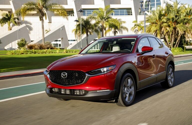 The front and side view of a red 2020 Mazda CX-30 driving down an open road.