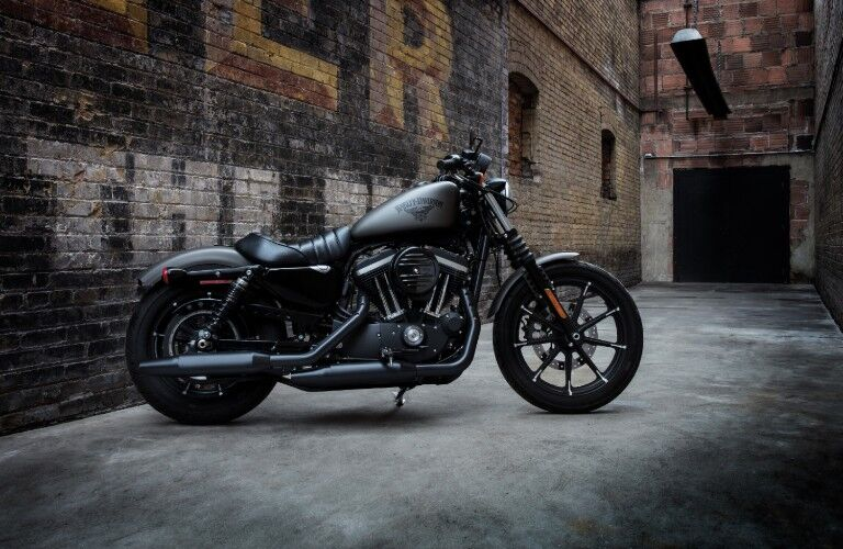 The side view of a black 2018 Harley-Davidson Iron 883 motorcycle parked in an alley.