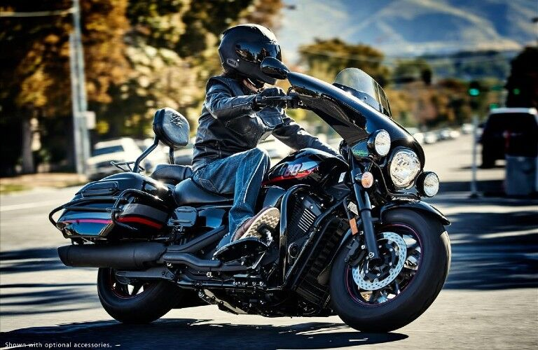 A black 2017 Yamaha V-Star 1300 Deluxe being driven by a man down the road.
