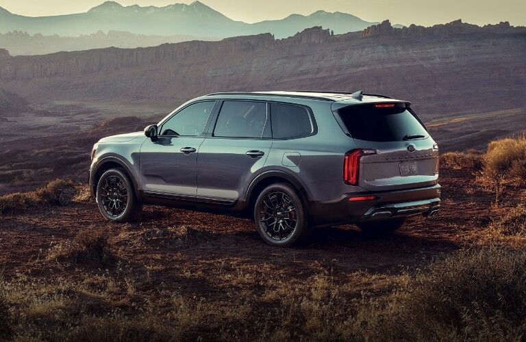 A 2021 Kia Telluride parked on a dirt area with rocky structures in the background