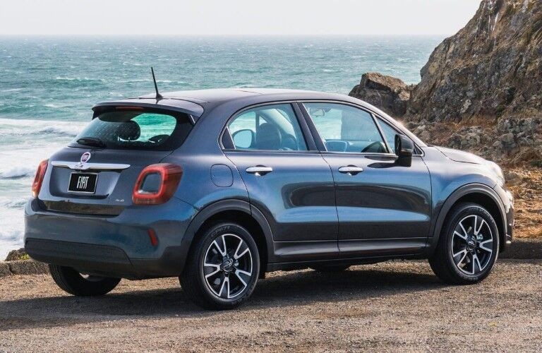 Rear passenger angle of a blue 2019 FIAT 500X parked by the ocean