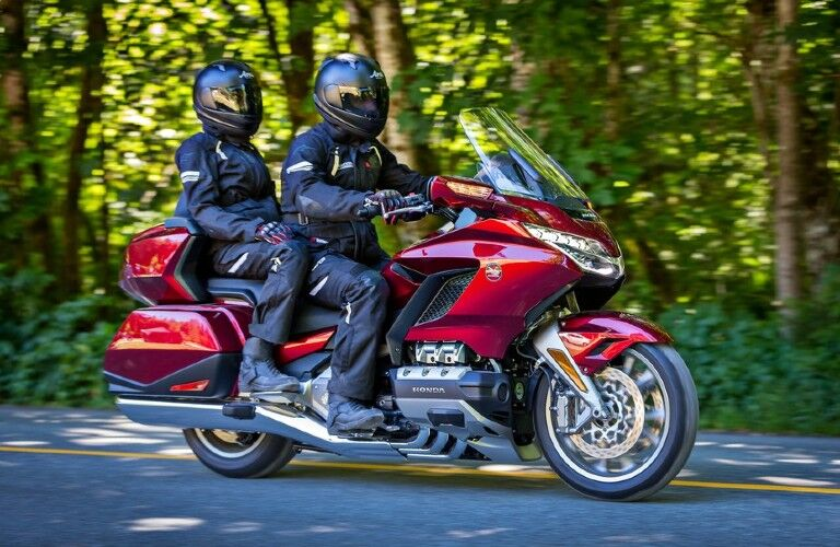 A couple riding on a red 2018 Honda Gold Wing.