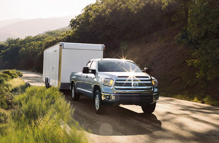 A front and side image of a silver 2016 Toyota Tundra hauling a trailer.