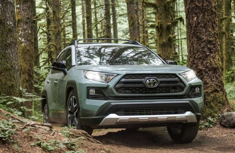 The front view of a light green 2021 Toyota RAV4 driving in a forest.