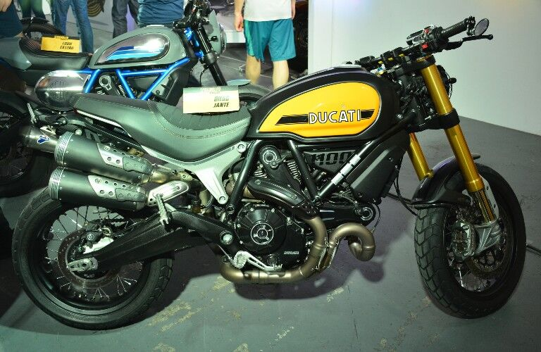 A vintage black and yellow Ducati Scrambler set up at a showcase.