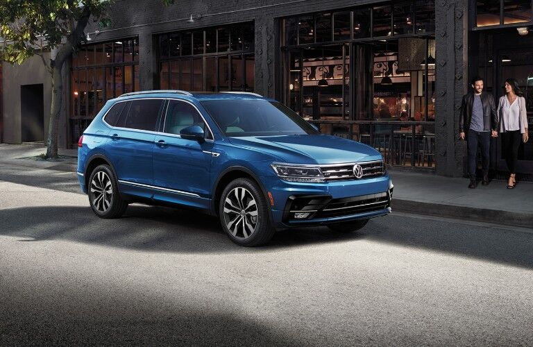Man and woman walking towards blue 2020 VW Tiguan