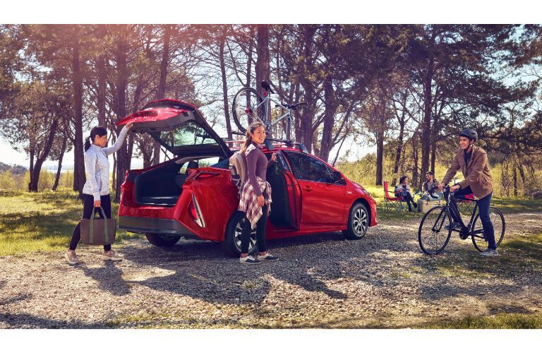 2020 Toyota Prius Prime exterior shot with red paint color parked on a gravel path in the woods with trunk up as a family unloads picnic materials and bikes
