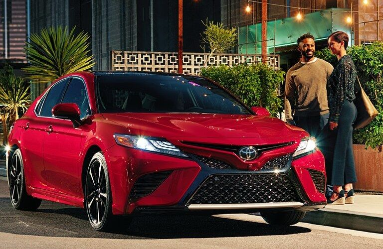 Front passenger angle of a red 2020 Toyota Camry with two people standing by it
