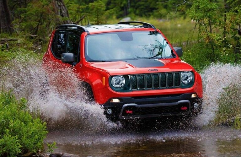 A 2021 Jeep Renegade driving through some water with trees and bushes on either side of the water