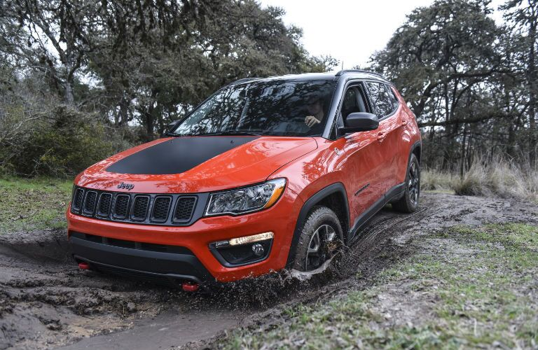 A front left quarter photo of the 2020 Jeep Compass going through the mud.
