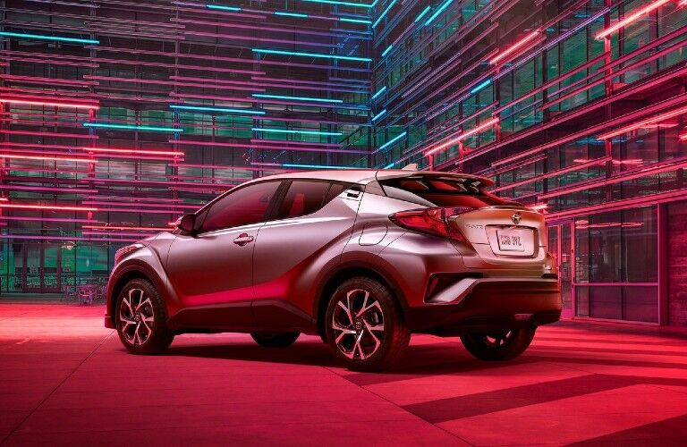 A read and side view of a gray 2020 Toyota C-HR with ambient lighting.