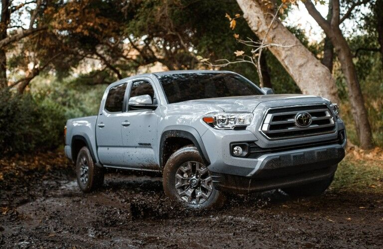 The front and side view of a silver 2021 Toyota Tacoma driving in the mud.