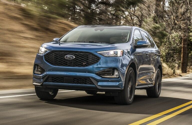 Front driver angle of a blue 2020 Ford Edge driving down a road