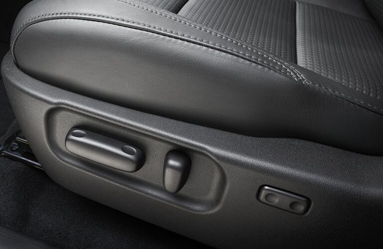 An image of the front power adjusted seating controls inside a 2020 Toyota Tacoma.
