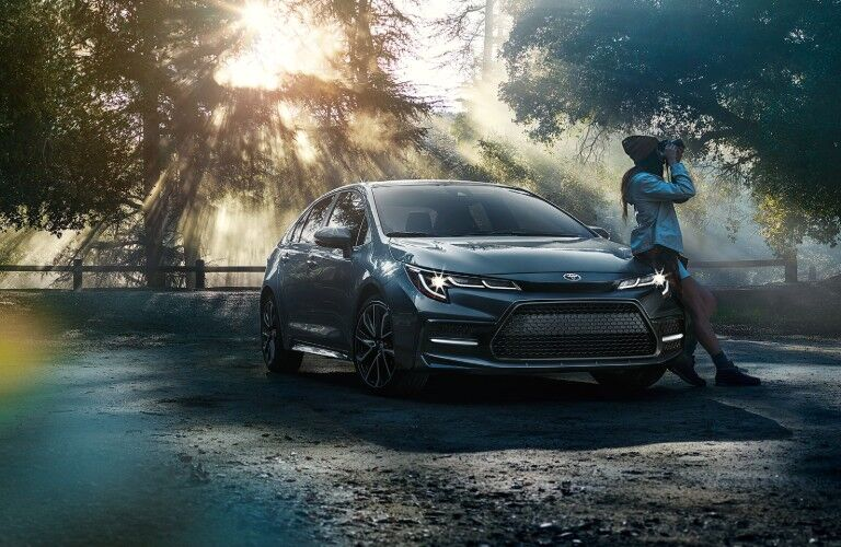 Front passenger angle of a blue 2020 Toyota Corolla parked outdoors with a person leaning on it photographing nature