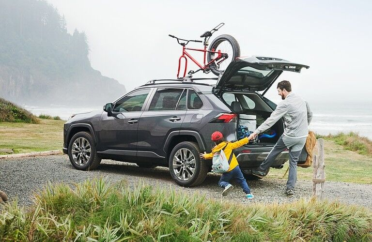 Rear driver angle of a grey 2020 Toyota RAV4 with a dad and child at the rear with the liftgate open