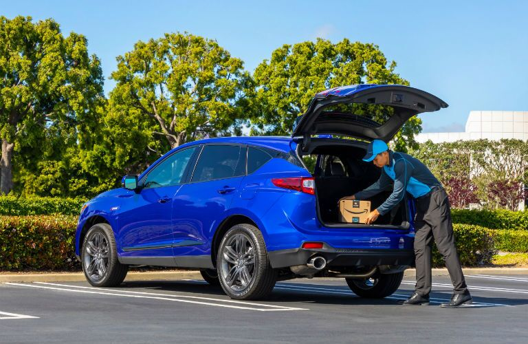 A photo of a delivery person loading a package into the back of the 2020 Acura RDX.