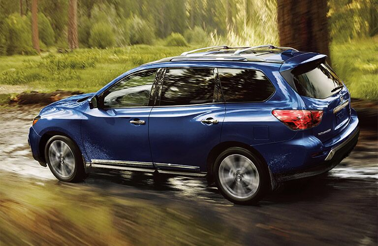 Blue 2020 Nissan Pathfinder driving near trees