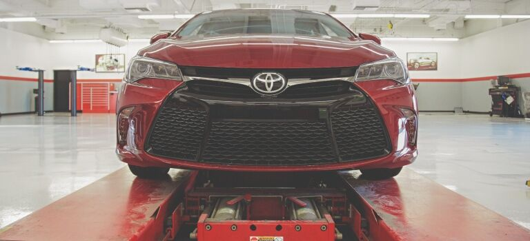 Toyota Camry red on a lift front view