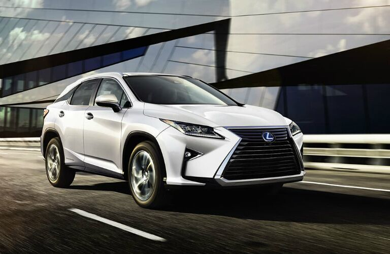 White 2019 Lexus RX L drives down a road past a futuristic glass building.