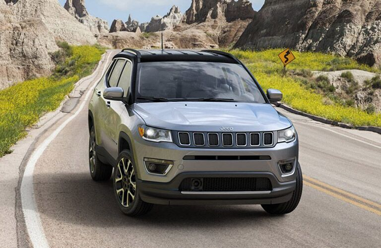 A frontal image of a gray 2020 jeep Compass driving down a rural road.
