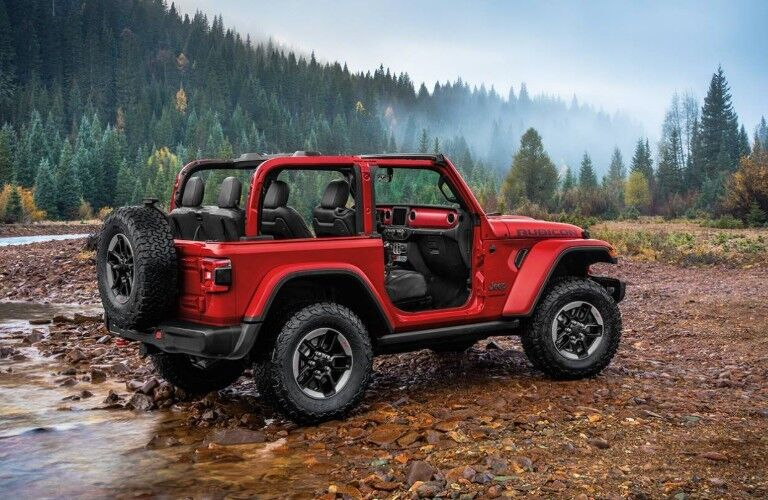 red jeep wrangler parked near forest