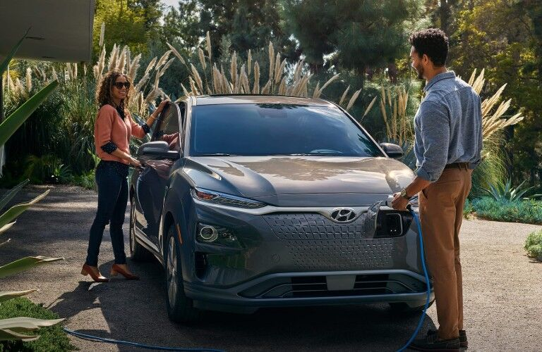 Front passenger angle of a grey 2019 Hyundai Kona Electric with a man charging it in front and a woman opening the passenger door